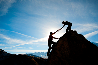 Two peope climbing mountain; hands are almost clasped as one helps the other up; managing movement