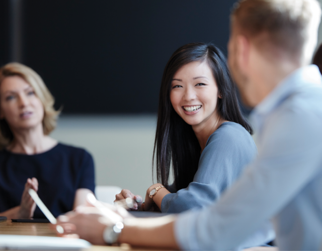 Young female professional smiling during group discussion