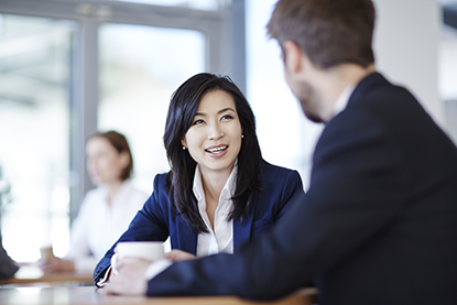 Smiling woman dark hair; navy suit; discussing with man beside her