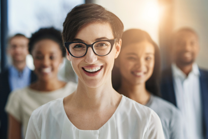 Young woman with glasses smiling with smiling co-workers standing behind her