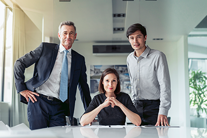 Portrait of confident business people at desk in board room in office