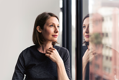 Thoughtful businesswoman looking through window reflecting on her experiences