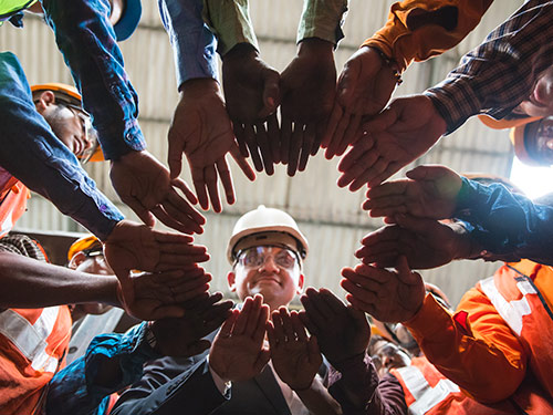 Group of manufacturing employees with hands in a cirlce