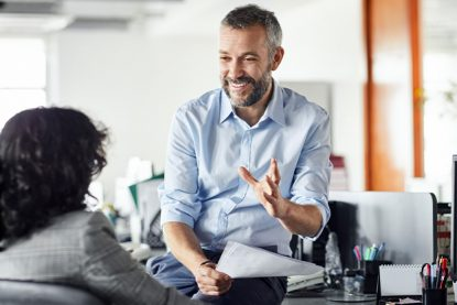Smiling businessman explaining strategy at office to help teammate in selling training