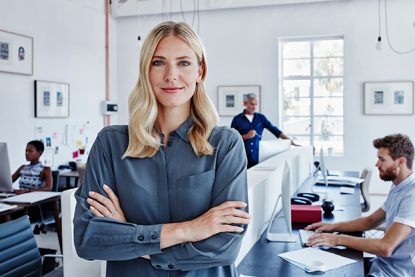 Portrait of confident businesswoman in office with staff in background