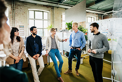 A small office team is talking together during a morning presentation with the manager.