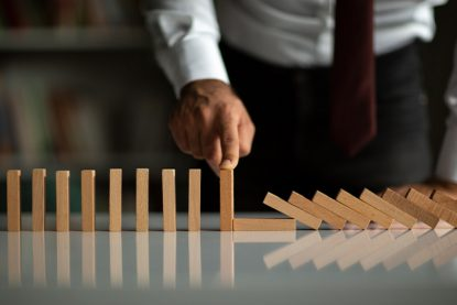 Businessman Stop Domino Effect. Leadership and Crisis Management Concept