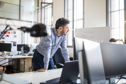 Thoughtful businessman leaning on desk by computer monitor while looking away at creative office