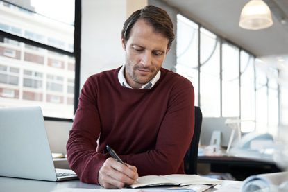 businessman taking notes on virtual learning content